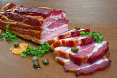 Sliced bacon with caper and parsley  against white Stock Photo
