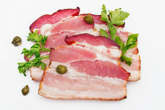 Sliced bacon with caper and parsley isolated against white Stock Photos