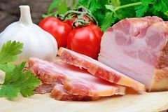 Sliced of bacon with cherry tomatoes, garlic and parsley on table Royalty Free Stock Image
