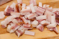 Sliced bacon cubes on the wooden cutting board Royalty Free Stock Photos