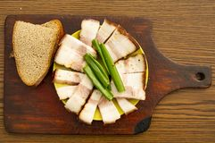 Sliced bacon with green onions on a cutting board stock photo
