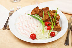 Sliced bacon. With onion and bread rusks on a dish in restaurant Stock Image