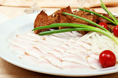 Sliced bacon. With onion and bread rusks on a dish in restaurant Royalty Free Stock Image