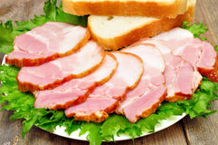 Sliced bacon. On a plate with bread Stock Photography