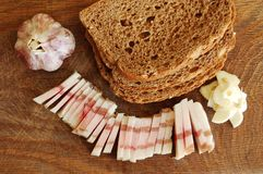 Sliced bacon of salty pork on a chopping board with garlic and bread Royalty Free Stock Photography