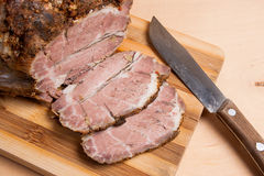Sliced baked pork with herbs and spice on wooden board. Royalty Free Stock Photos