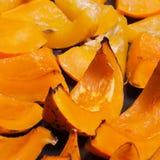 Sliced of baked vivid orange colour pumpkin on the baking sheet Stock Photos