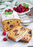 Sliced banana bread with raspberries, cherries and white chocolate. On parchment Stock Photos
