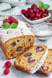 Sliced banana bread with raspberries, cherries and white chocolate. On parchment, vertical Royalty Free Stock Photography