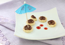 Sliced banana with chocolate and cocktail umbrella. Five slices of banana decorated with chocolate topping, strawberry marmalade and a blue cocktail umbrella stock images