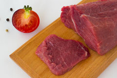 Sliced beef on a cutting board. Tomato and pepper Royalty Free Stock Photography