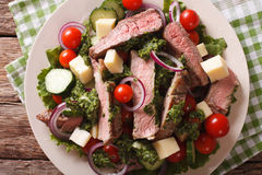 Sliced beef steak with a salad of fresh vegetables close-up. Hor Stock Photos
