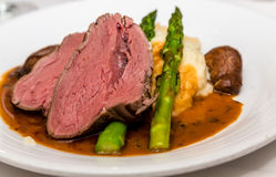 Sliced Beef Tenderloin with Asparagus. Sliced tenderloin of beef on mashed potatoes with asparagus and gravy royalty free stock image