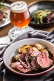 Sliced Beef tenderloin roasted steak potatoes rosemary and draft beer stock photography