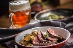 Sliced Beef tenderloin roasted steak potatoes rosemary and draft beer stock photos