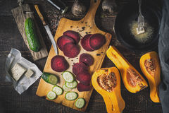 Sliced beet with vegetable and  pan with butter on the wooden table top view Royalty Free Stock Photo