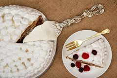 Sliced biscuit cake decorated with whipped cream and raspberries. Silver cake lifter beside it on table with sackcloth. Top view Stock Images