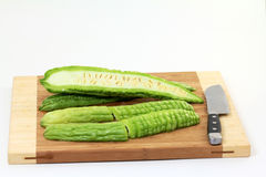 Sliced Bitter Melons. (Momordica charantia) or ampalaya on chopping board; white background royalty free stock photography