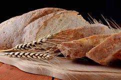 Sliced black bread on a cutting board, ears of wheat. Stock Photo