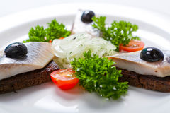 Sliced black bread and herring on a white plate stock photography