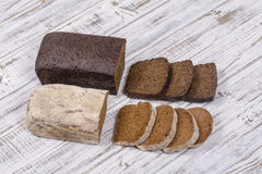 Sliced black bread on white wooden background. Close up Stock Photos