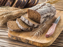 Sliced black bread on the wooden plank. Royalty Free Stock Images