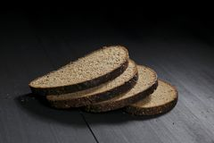 Sliced black bread on wooden table Stock Photos