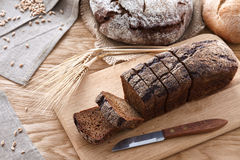 Sliced black bread on a wooden table. Sliced black rye bread with wheat and rye ears on a wooden table royalty free stock image