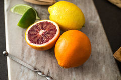 A sliced blood orange sits on a cutting board with lemon, lime, and tangerine. Stock Photos