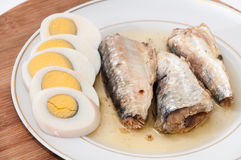 Sliced boiled egg and sardines served on the plate Stock Photos