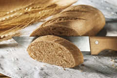 Sliced bread. With wooden knife on white cloth Stock Photography