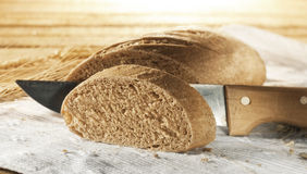 Sliced bread. With wooden knife on white cloth Royalty Free Stock Photos