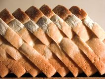 Sliced Bread. Sliced white crusty bread, on a bread board royalty free stock photography
