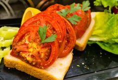 Sliced bread , baked tomatoes and fresh parsley and salad stock photo