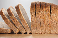 Sliced bread at a board. Loaf of sliced bread at a wooden board Royalty Free Stock Image
