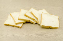 Sliced bread on brown wood Stock Photography
