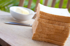 Sliced bread with butter on an outdoor setting. Royalty Free Stock Images