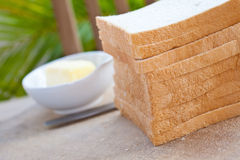 Sliced bread with butter on an outdoor setting. Stock Photo
