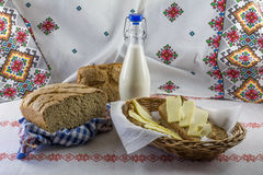Sliced bread and butter in a wicker basket and a bottle milk. Royalty Free Stock Images