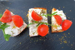 Sliced bread with creamed cheese & mini tomatoes. Cherry tomatoes on a bred slice with oregano and green salad stock image