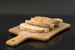 Sliced bread on cutting board. And black background Royalty Free Stock Images