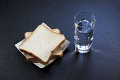 Sliced bread and drinking water. Table ready for breakfast with drinking water and bread Royalty Free Stock Images