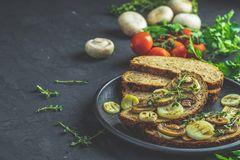 Sliced bread with fried cutting mushroom champignon and onion. Delicious homemade whole grain rye sliced bread toast with fried cutting mushroom champignon and stock photography
