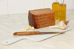 Sliced bread,garlic and olive oil on kitchen table. Royalty Free Stock Images