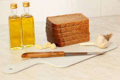 Sliced bread,garlic and olive oil on white kitchen. Royalty Free Stock Photos