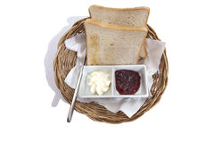 Sliced bread jam and butter silverware. Sliced bread, jam and butter breakfast in rattan tray on Dinning table Royalty Free Stock Images