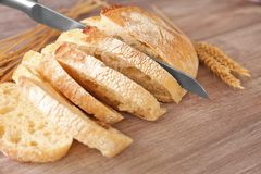 Sliced bread with knife and wheat spikes o Stock Photo