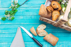 Sliced bread and other baked in a wooden box on a turquoise tabl. Slices of bread and a knife lying on a turquoise wooden table with a napkin and a sprig of stock photography