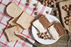 Sliced bread in plate with chocolate cream and nuts. Sliced bread with chocolate cream on kitchen table with hazelnuts Royalty Free Stock Photos