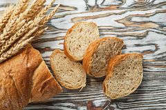 Sliced bread ripe rye ears on wooden surface Royalty Free Stock Photography